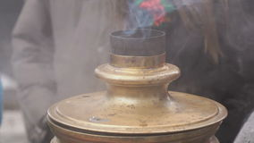 People standing around russian boiling samovar stock video