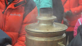 People standing around russian boiling samovar stock footage