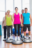 People standing on balance balls in gym. Full length portrait of people standing on balance balls in gym Stock Images