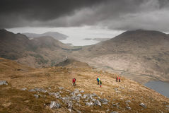 People Standing on Brown Mountain Near Lake Under Gray Clouds during Day Time Royalty Free Stock Photos