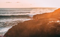 People Standing on Cliff Near Body of Water Golden Hour Photography Stock Photos