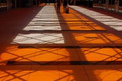People Standing at a Distance Under Orange and White Lighted Building Stock Images