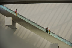 People standing on escalator in shopping mall Royalty Free Stock Photo