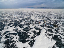 People standing on the ice of Lake Baikal, covered with snow. Siberia, Russia. Winter Lake Baikal, ice covered with snow, shooting from a drone Royalty Free Stock Photo