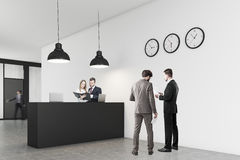 People standing near an office counter with three clocks Royalty Free Stock Images