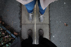 People standing over greenwich meridian line. Two people's feet seen standing over greenwich meridian line Royalty Free Stock Photo