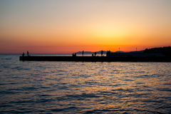 People standing on pier in sunset Royalty Free Stock Image
