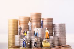 People standing on a pile of coins. Inequality and social class. stock images