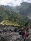 People are standing in a queue on  peak Giewont Stock Images