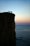 People standing on the rock across the sea silhouettes Royalty Free Stock Image