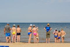 People standing on sand near sea Royalty Free Stock Photos