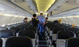 People standing and sitting in an airplane royalty free stock photos