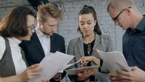 People standing together in office and checking agreement or doc. Concept group of people in small business. Busy employee manager standing together in office stock video