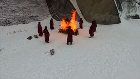 People stay around the campfire. Footage. People stay around the fire at night. group of monks near the fire in the royalty free stock photo