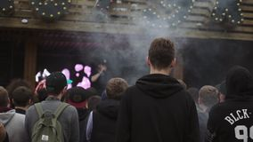 People stay on street in front stage. Festival vapers. Audience. Steam. Host. Slow motion stock video footage