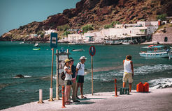 People are staying at a bus stop and waiting for a bus near Akrotiri town on Santorini island. Royalty Free Stock Image