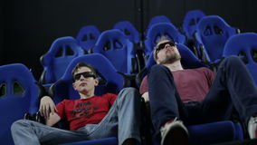 People in stereo glasses sit at cinema watch movie. People in stereo glasses sit at cinema and watch movie with chair shake effects for motion imitation stock footage
