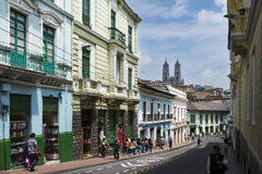 People in a street in the historic center of the city of Quito, in Ecuador, with the Basilica of the National Vow on the backgroun Stock Photo
