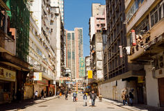 People on a street with tall scyscrapers with concrete walls in busy district Royalty Free Stock Image