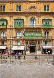 People at street with traditional green balconies Valletta. Valletta, Malta - April 3, 2014:  People at the street with traditional green balconies, Valletta old Stock Image