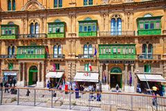 People on street with traditional green balconies Valletta. Valletta, Malta - April 3, 2014:  People on the street with traditional green balconies, Valletta old Royalty Free Stock Image