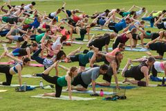 People Stretch Right Leg In Unison At Outdoor Yoga Class. Atlanta, GA, USA - July 2, 2017:  Dozens of people grab their right leg and stretch as they take part Stock Photography