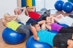People stretching on exercise balls in fitness club Stock Photos