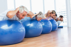People stretching on exercise balls in gym Stock Photography