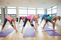 People stretching hands at yoga class in fitness studio Stock Images