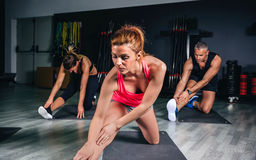 People stretching legs in a fitness class Stock Photography