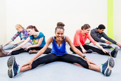 People stretching legs in gymnastics gym Stock Images