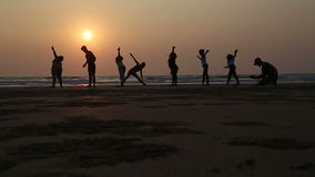 People stretching at a sandy beach in Goa at sunset, with man photographing. stock video