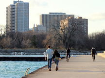 People Stroll and Bike at Montrose Harbor, Chicago. People are shown strolling and biking along Lake Michigan at Montrose Harbor, Chicago, with high rise Stock Images