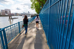 People strolling and jogging along the river Thames in London, UK stock photo
