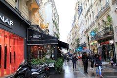 People strolling through the rain, holding umbrellas, near famous restaurant, L'Escargot, Paris, France,2016 Royalty Free Stock Images
