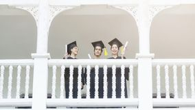 People students in the feeling of happy and graceful. With the graduation gowns and cap stand in the line at corridor of classic building stock images