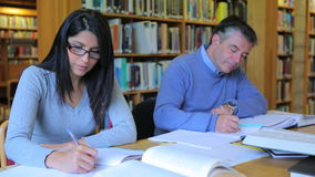 People studying in library. Mature students studying in the library stock video footage
