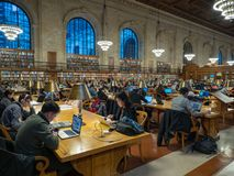 People studying in the Rose Reading Room of the NYPL stock photo