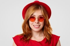 People, style and beauty concept. Adorable young female model in red outfit and sunglasses, has gentle smile, shows white even tee royalty free stock photos