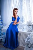 People, style, holidays, hairstyle and fashion concept - happy young woman or teen girl in blue dress stock image