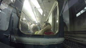 People in the subway car through the glass. In the way. Footage is Suitable for group, crowd, blurred, wires, cables, window in the window, reflection stock video
