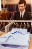 People in suit shop. Folded classical man shirts lying on the shelf, modern young handsome businessman choosing classical suit in the suit shop in the background Stock Photo