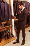 People in suit shop. Modern young handsome businessman looking and choosing classical shoes in the suit shop Stock Image
