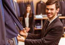 People in suit shop. Modern young handsome businessman smiling and choosing classical suit in the suit shop, while a young beautiful female shop assistant Stock Photography