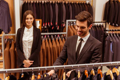 People in suit shop. Modern young handsome businessman smiling and choosing classical suit in the suit shop, while a young beautiful female shop assistant Royalty Free Stock Photos