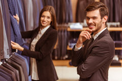 People in suit shop. Modern young handsome businessman smiling and standing in the suit shop, while a young beautiful female shop assistant smiling and offering Royalty Free Stock Photography