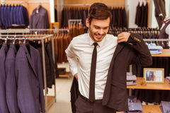 People in suit shop. Modern young handsome businessman smiling and trying on classical suit in the suit shop Stock Images