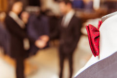 People in suit shop. A part of a mannequin with a bright red bow tie, young beautiful female shop assistant consulting a modern young handsome businessman in the Stock Photography