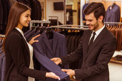 People in suit shop. Young beautiful female shop assistant consulting a modern young handsome businessman in the suit shop Stock Images