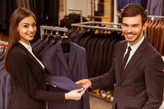 People in suit shop. Young beautiful female shop assistant consulting a modern young handsome businessman in the suit shop Royalty Free Stock Photography